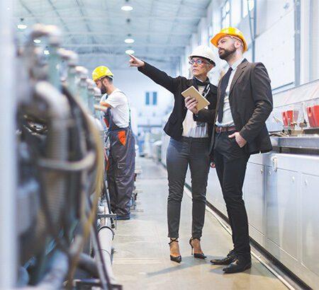 Zwei Männer besichtigen eine Produktionshalle in einem Unternehmen. Beide tragen einen Helm, der Mann links zeigt auf etwas und erklärt dem anderen, was es ist.