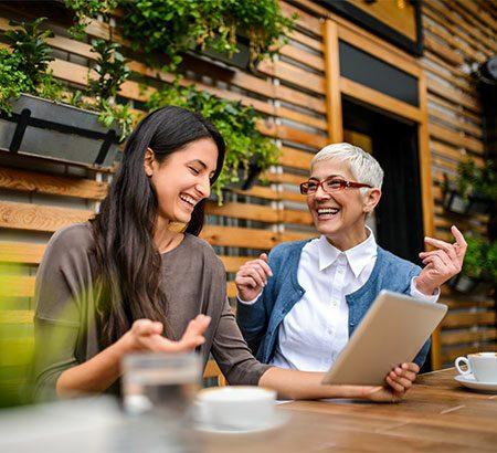 Junge Frau sitzt mit Tablet am Tisch und ist im Business-Talk mit einer älteren Dame links neben ihr.