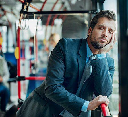 Mann lehnt sich im Bus ans Fenster und träumt