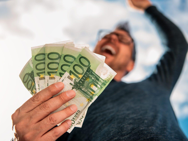 Mann mit mehreren 100-Euro-Scheinen in der Hand