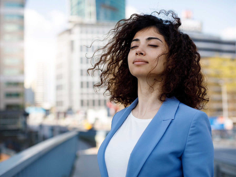 Frau auf Straße sieht optimistisch nach vorne
