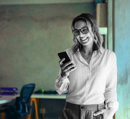 Eine Frau schaut lächelnd auf ihr Smartphone.