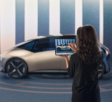 Eine Frau die ein Foto von einem futoristischem Auto macht