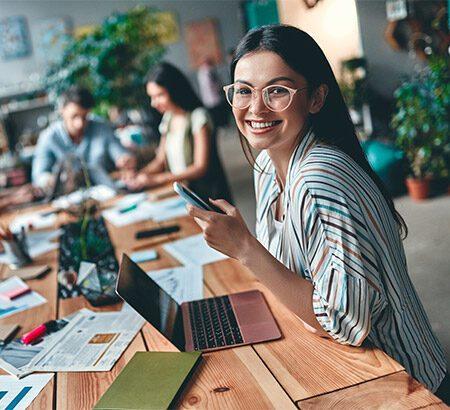 Frau sitzt am Arbeitsplatz und lächelt in die Kamera